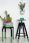 Black and green painted stools and baskets as planters