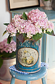 Pink-flowering hydrangea in old tin