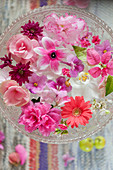Pale pink and deep pink flowers floating in glass dish