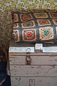Häkeldecke mit Granny Squares auf einer alten Holzkiste