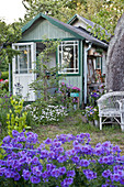 Picturesque summerhouse in flowering summer garden