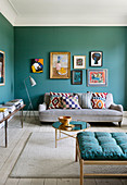 A picture gallery above a sofa in a living room with petrol blue walls