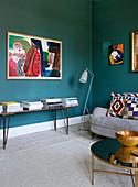 Bank mit Bücherstapeln im Wohnzimmer mit petrolblauen Wänden
