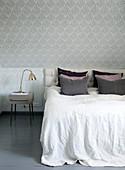 Schlafzimmer mit Vintage-Tapete und Bett im Kniestock