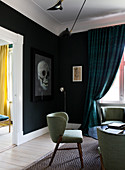 Retro armchair in living room with black wall and skull picture
