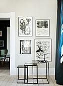 Filigrane, kubische Beistelltische vor Bildergalerie mit Zeichnungen