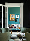 Upholstered chairs in retro style, a view of the living room with a petrol blue wall