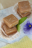 Honey soap in muffin cases with verbena leaves and pansies