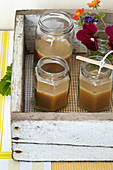 Homemade candles in screw jars in a wooden box