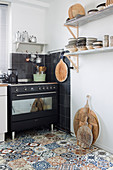 Mediterranean kitchen with patterned tiled floor and black stove