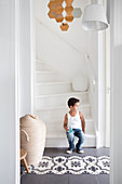Boy sitting on white stairs in a hallway with patterned tiles