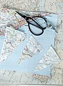 Ausgeschnittene Dreiecke aus Landkarten für eine Wimpelkette