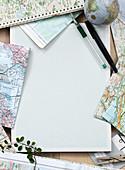 Leeres Blatt Papier, Stifte und Landkarten zur Reiseplanung