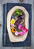 Sweet pea, marigold, chrysanthemum, and borage in a wooden bowl with water