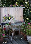 Rustikaler Sitzplatz auf der Terrasse mit Bretterwand und Sommerblumen