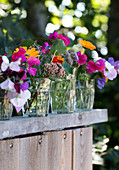 Summer flowers in water glasses on a wooden wall