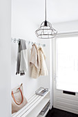 Door with window and clothing rod as an entryway area in white