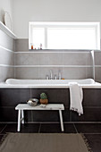 White bench in front of the bathtub under the horizontal window