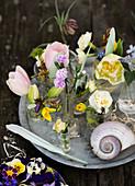 Frühlingsblumen in verschiedenen Glasväschen auf einem Tablett