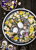 Wreath of roses, daffodils, viburnum, and grape hyacinths on a tray