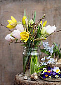 Easter bouquet with tulips, daffodils, and hazel branches in a screw-top jar