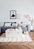 Alte Holzkiste als Couchtisch vor grauem Sofa auf Fischgrätparkett