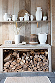 Shelf with white jugs above the console with firewood