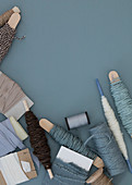 Cord, sewing thread, and fabric ribbons in blue-gray and natural tones