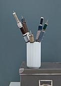 Vase mit Garnrollen auf Stricknadeln