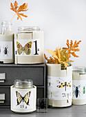 Mit Schmetterling-Motiven beklebte Papiermanschetten um Schraubgläser