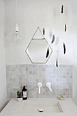 Mobile made of feathers and a hexagonal mirror over the sink