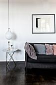 Graues Polstersofa mit Kissen, Beistelltisch, darüber Pendelleuchte im Wohnzimmer