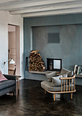 A cosy chair on a concrete floor in front of a fireplace in a blue wall