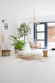 Hanging chair and houseplants in front of the patio door in a white living room