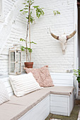 Wooden bench with pillows and antlers on terrace with whitewashed brick wall