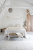 A double bed in a white bedroom with wooden accents
