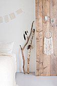 Dream catcher on a wooden wall in white bedroom