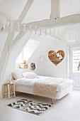 Weißes Schlafzimmer im Dachgeschoß, Herz aus Holz an der Wand