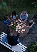 Kinder um runden Gartentisch mit selbstgemachten Windlichtern