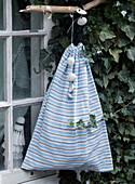 Homemade sack made of striped fabric hangs on the window
