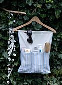 Selbstgemachtes Badutensilo aus blau gestreiftem Stoff am Kleiderbügel