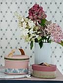 Mit Stoffbändern beklebte Schachteln und Vase mit verschiedenen Hortensien