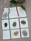 Säckchen mit Stoffbändern und bemalte Steine als Spiel