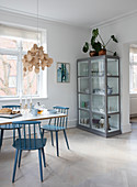 Blue sprouted chairs at the dining table in front of a glass cabinet with crockery