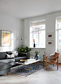 A grey sofa and a leather chair in a simple living room with a white floor