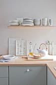 A shelf of crockery above a kitchen work surface
