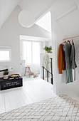 Clothes rail, vintage box, and stool in front of a window in the bright attic