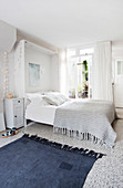 A blue rug in front of double bed with grey knitted blanket