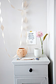 Wooden cupboard with flower and bowl, above a message and paper garland