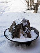 Firewood in a fire bowl with fairy lights in a snowy garden